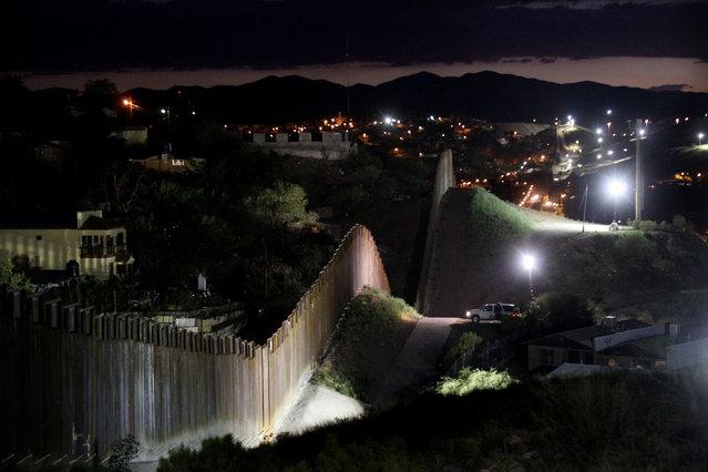 The border wall is illuminated at night July 6, 2012 in Nogales, Arizona
