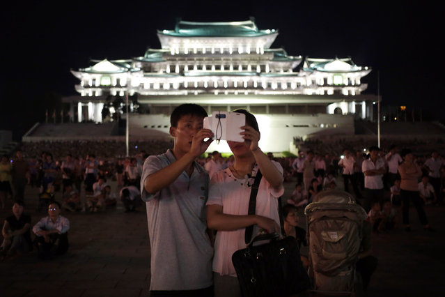 A North Korean couple use their smart phone to photograph fireworks, Sunday, July 27, 2014 in central Pyongyang, North Korea. (Photo by Wong Maye-E/AP Photo)