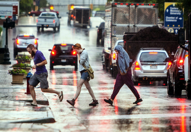 Pedestrians cross Main Street in downtown Harrisonburg, Va., after a sudden downpour begins to taper off Thursday, June 23, 2016. Heavy rainfall has caused flooding in other parts of the state. (Photo by Daniel Lin/Daily News-Record via AP Photo)