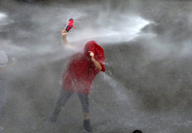 A Lebanese protester is sprayed with water during a protest against corruption and rubbish collection problems near the government palace in Beirut August 22, 2015. (Photo by Jamal Saidi/Reuters)