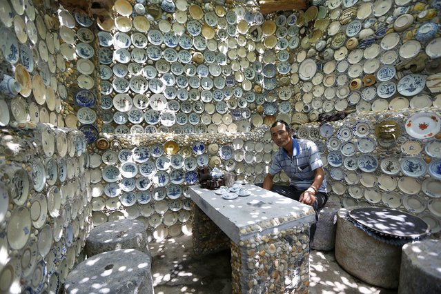 Nguyen Van Truong, 52, sits in his house covered by antique dishes, in Son Kieu village, Chan Hung commune, Vinh Phuc province, some 80 km from Hanoi, Vietnam, 06 August 2014. Nguyen Van Truong, a veteran, has been collecting antiques for over 20 years. Truong has started to attach all of his antiques to the walls and around his house in 2000.(Photo by Luong Thai Linh/EPA)