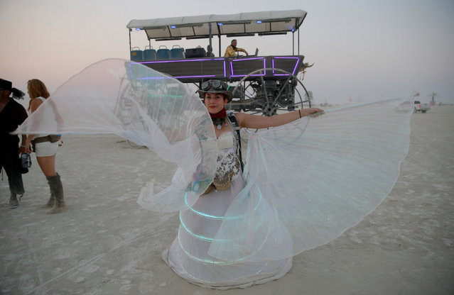 Burning Man participant Jennifer Seiler dances to the music of an art car with her ornate dress that she wore to a wedding in the middle of the desert during the 4th day of the annual Burning Man arts and music festival in the Black Rock Desert of Nevada, U.S. on September 1, 2017. (Photo by Jim Urquhart/Reuters/Splash News and Pictures)