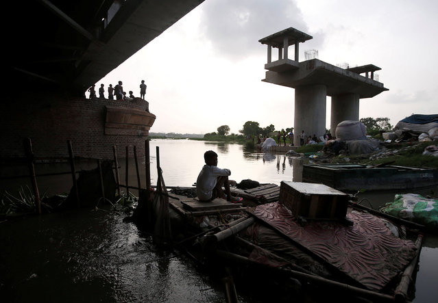 A boy sits on a handmade boat outside his makeshift home under a railway bridge over the river Yamuna in the old quarters of Delhi, India, July 19, 2016. (Photo by Adnan Abidi/Reuters)