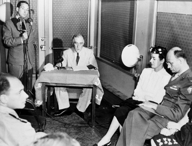 U.S. President Franklin D. Roosevelt accepts his Democratic nomination for a fourth term in the White House via radio from a railroad car at a Pacific Coast Naval Station, July 20, 1944. Seated at right are his son, Col. James Roosevelt, and his daughter-in-law Romelle Theresa Schneider. (Photo by AP Photo)
