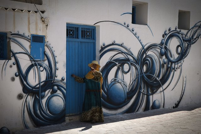 """A woman enters her house decorated by French artist REA in the village of Erriadh, on the Tunisian island of Djerba, on August 8, 2014, as part of the artistic project """"Djerbahood"""". (Photo by Joel Saget/AFP Photo)"""