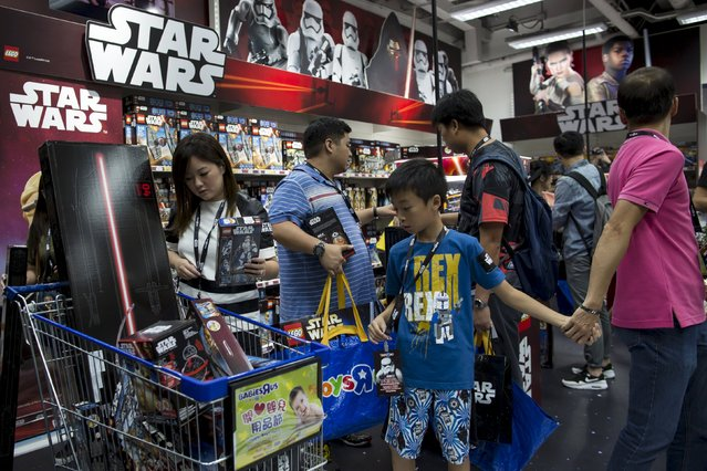 """Customers pick new toys from the upcoming film """"Star Wars: The Force Awakens"""" on """"Force Friday"""" in Hong Kong, China, September 4, 2015. New """"Star Wars"""" toys and other merchandise were released in stores across Hong Kong just after midnight local time during a global rollout of the popular products. (Photo by Tyrone Siu/Reuters)"""