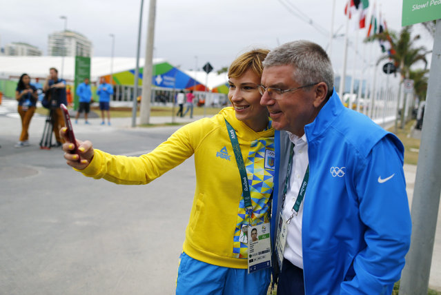 Tomas Bach, President of the International Olympic Committee, poses for a selfie with Ukrainian air pistol athlete Olena Kostevych before moving into the Olympic village in Rio de Janeiro, Brazil, July 28, 2016. (Photo by Ivan Alvarado/Pool Photo via AP Photo)