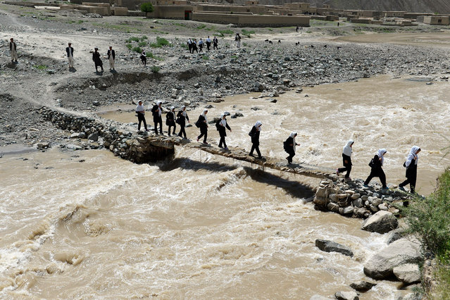 Afghan schoolgirls cross a wooden bridge in Qara Zaghan village in Baghlan province on May 7, 2013. (Photo by Shah Marai/AFP Photo)