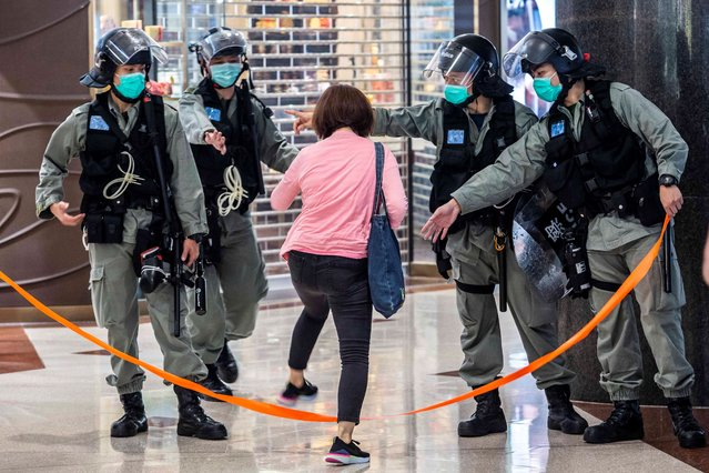 Riot police wear face masks, as a precautionary measure against the COVID-19 coronavirus, allow a women to cross a cordon after a protest by pro-democracy demonstrators at a shopping mall in Hong Kong on May 9, 2020. (Photo by Isaac Lawrence/AFP Photo)