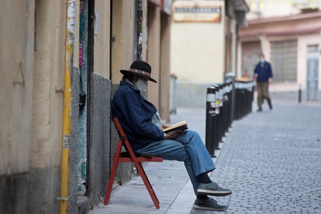 A man wearing a face mask to protect against coronavirus sits and waits for customers outside a small shop while reading a book in Madrid, Spain, Saturday, May 16, 2020. Spanish Prime Minister Pedro Sanchez is trying to calm business owners and workers in Spain's critical tourism industry that are afraid their livelihoods are under extreme threat from the coronavirus lockdown as Spain is slowly scaling back confinement measures. (Photo by Paul White/AP Photo)