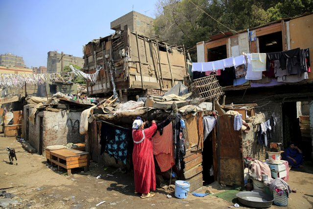 A woman washes her clothes in the Eshash el-Sudan slum in the Dokki neighbourhood of Giza, south of Cairo, Egypt September 2, 2015. (Photo by Amr Abdallah Dalsh/Reuters)