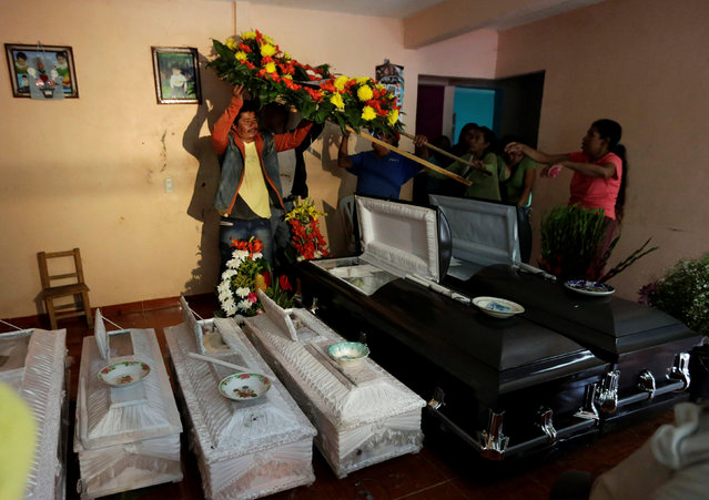 People carry a floral wreath next to coffins of relatives killed after a mudslide, in the aftermath of Tropical Storm Earl in the town of San Miguel Xaltepec, in Puebla state, Mexico, August 8, 2016. (Photo by Henry Romero/Reuters)