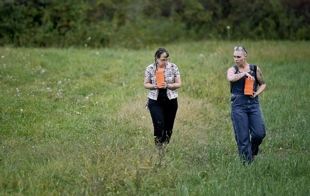 In this October. 8, 2017, photo, Zora Gussow, left, and Emily Lynch collect unbroken clay targets from after a shooting session of the Trigger Warning Queer & Trans Gun Club in Victor, N.Y. The gun club members stress they are about empowerment and self-defense, not offense. They say it also gives them a sense of community, even if it comes on a firing line in the middle of farm country. But some veteran activists say they're concerned that this will add to an unnecessary arms race and eventually cause more danger. (Photo by Adrian Kraus/AP Photo)