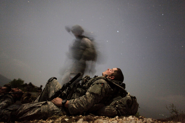 A U.S. soldier of 2-12 Infantry 4BCT-4ID Task Force Mountain Warrior takes a break during a night mission near Honaker Miracle camp at the Pesh valley of Kunar Province August 12, 2009. (Photo by Carlos Barria/Reuters)