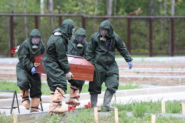 Grave diggers wearing protective suits carry a coffin during the burial of a COVID-19 victim at a cemetery on the outskirts of Moscow, Russia on May 15, 2020. (Photo by Kirill Zykov/Moscow News Agency/Handout via Reuters)