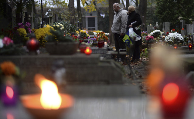 People stop in front of a grave at the Powazki cemetery in Warsaw, Poland, Wednesday, November 1, 2017. Candles and flowers cover tombstones in graveyards across Poland on All Saints' Day, as people honour the saints and their departed friends and family, in Christian tradition. (Photo by Alik Keplicz/AP Photo)