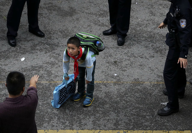 A school boy carrying his bags is surrounded by police officers as he walks out the school gate after a stampede at Mingtong Primary School in Kunming in southwest China's Yunnan province Friday, September 26, 2014. Six schoolchildren died in the stampede, authorities said. It wasn't clear what caused the stampede among the first- and second-grade students of the primary school, the city's propaganda office said on its microblog. (Photo by AP Photo)