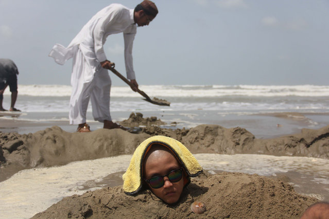 Pakistani children are seen half buried at seaside during the solar eclipse to in Karachi, Pakistan on 21,June 2020. Some Pakistani people hope that burying is ailing people during solar eclipse. (Photo by Sabir Mazhar/Anadolu Agency via Getty Images)