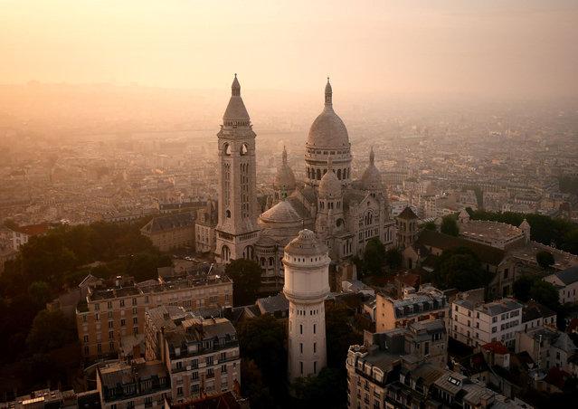 Sacré Cœur glowing in a hazy sunrise, Paris, France. (Photo by Amos Chapple/Rex Features)