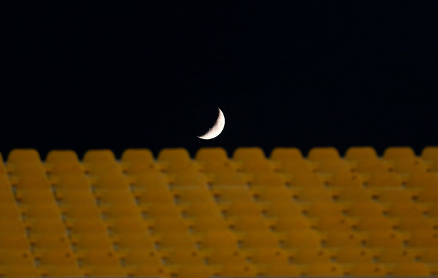 Football Soccer, Egyptian Premier League, Al Ahly vs El Zamalek, Army Stadium, Suez, Egypt on July 9, 2016. The moon is seen behind seats, which are empty due to security reasons, before the start of the match. (Photo by Amr Abdallah Dalsh/Reuters)