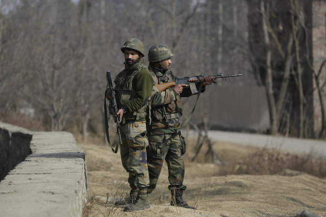 Indian army soldiers guard during a gunbattle at Pakharpore village, south of Srinagar, Indian controlled Kashmir, Thursday, November 30, 2017. At least five rebels were killed and three civilians and a soldier injured on Thursday in armed confrontations and anti-India protests in the disputed region, officials said. (Photo by Mukhtar Khan/AP Photo)