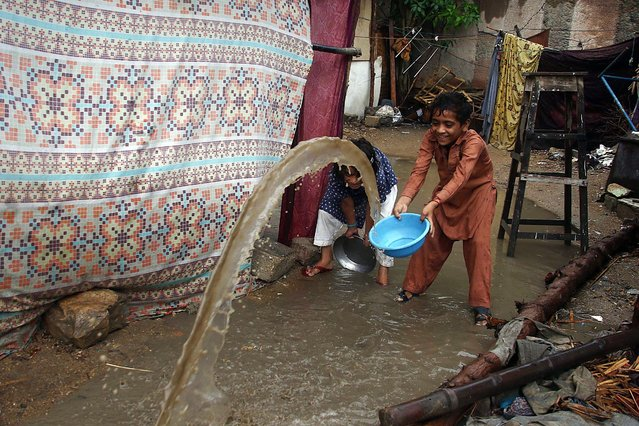 A boy removes rain water from his hut after a heavy downpour in Karachi, Pakistan, 28 August 2016. Heavy monsoon rains across the country has claimed dozens of lives in last few weeks as Pakistan Meteorological Departmen office predict more rains in coming days. (Photo by Shahzaib Akber/EPA)