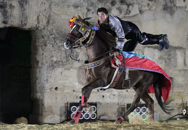 """A performer rides a horse during the """"La nuit du cheval"""" (night horse) equestrian show, organised by the Ministry of Culture, at the Roman Amphitheatre of El Jem in Mahdia Governorate October 11, 2014. (Photo by Anis Mili/Reuters)"""