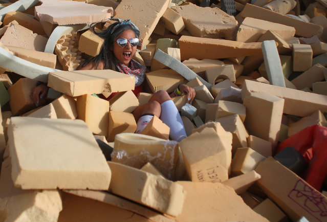 Lulu, her Playa name, falls into a foam pit as approximately 70,000 people from all over the world gather for the 30th annual Burning Man arts and music festival in the Black Rock Desert of Nevada, U.S.  September 1, 2016. (Photo by Jim Urquhart/Reuters)