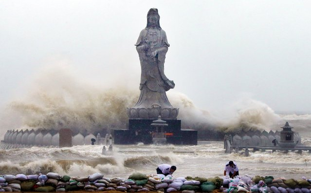 People set up sand bags to reinforce an embankment in front of an Avalokitesvara Bodhisattva statue as waves brought by Typhoon Dujuan slam the coastline in Quanzhou, Fujian province September 29, 2015. China ordered tens of thousands of boats back to shore and closed tourist attractions as a typhoon made landfall in the eastern province of Fujian early on Tuesday after leaving two dead and hundreds injured in Taiwan. (Photo by Reuters/China Daily)