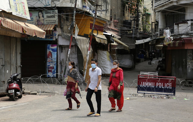 Indians wearing face masks as a precaution against the coronavirus walk past closed market during reimposed weekends lockdown to prevent the spread of new coronavirus in Jammu, India, Saturday, July 25, 2020. India is the third hardest-hit country by the pandemic in the world after the United States and Brazil. (Photo by Channi Anand/AP Photo)