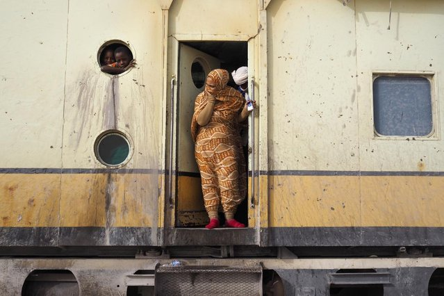 Passengers take a break while travelling on a SNIM train carrying iron ore and mine workers across the desert outside Nouadhibou June 25, 2014. (Photo by Joe Penney/Reuters)