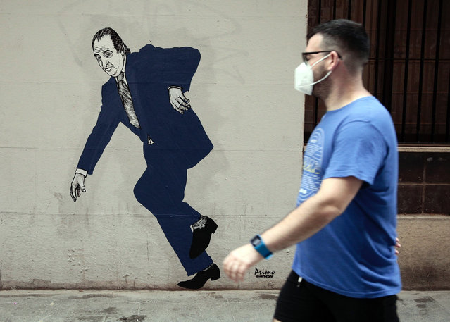 A person walks past graffiti by arstist selfnamed El Primo de Bansky (the cousin of Bansky) of former Spanish King Juan Carlos in Valencia, Spain, 05 August 2020. The Spanish Royal Household has announced that Emeritus King Juan Carlos I has proclaimed his intended decision to move abroad so as to not interfere in the image of the Spanish monarchy due to his alleged implication in a Swiss offshore account investigation. (Photo by Biel Aliño/EPA/EFE)