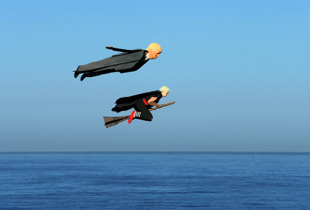 Remote control planes resembling U.S. Presidential candidate Donald Trump and Hillary Clinton fly over surfers in Carlsbad, California, U.S. September 15, 2016. (Photo by Mike Blake/Reuters)