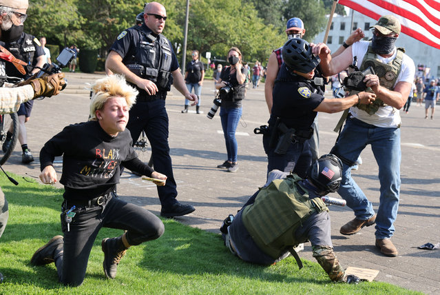 Police officers break up a fight between supporters of U.S. President Donald Trump and Black Lives Matter protesters outside the Oregon State Capitol building in Salem, Oregon, U.S. September 7, 2020. (Photo by Carlos Barria/Reuters)