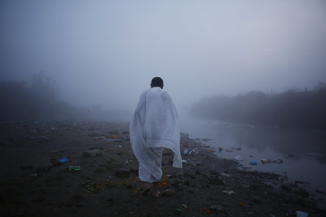 A Nepalese devotee walks towards the Bagmati river to perform rituals during Gaya Aunsi Festival in Kathmandu, Nepal, Monday, December 18, 2017. In this festival,  people gather and perform holy rituals to offer prayers and pay tribute to the deceased family member. Also, believed that doing this will help departed soul to find the way to the heaven. (Photo by Niranjan Shrestha/AP Photo)
