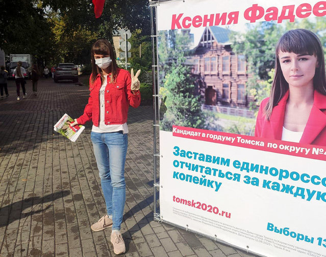 In this August 2020 photo provided by Alexei Navalny's team, Ksenia Fadeyeva, who is running for the city council in Tomsk, Russia, poses for a photo next to her election poster. Fadeyeva has secured a seat in the city council, according to preliminary results of the regional election that took place on Sunday, September 13, 2020. (Photo by Andrei Fateyev/Alexei Navalny's team via AP Photo)