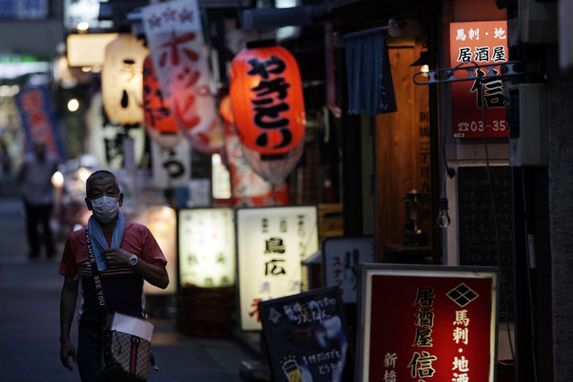 A man wearing a face mask to help curb the spread of the coronavirus walks down a bar street, Thursday, September 10, 2020, in Tokyo. The Japanese capital confirmed more than 270 coronavirus cases on Thursday. (Photo by Eugene Hoshiko/AP Photo)