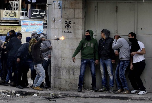 Palestinians take cover during clashes with Israeli troops in  the West Bank city of Hebron, following the death of Arafat Jaradat, a Palestinian prisoner held in an Israeli jail, on February 24, 2013. The death of the 30-year-old Palestinian after interrogation by Israel's Shin Bet security service stokednew West Bank clashes, along with Israeli fears of a third Palestinian uprising. (Photo by Nasser Shiyoukhi/Asociated Press)