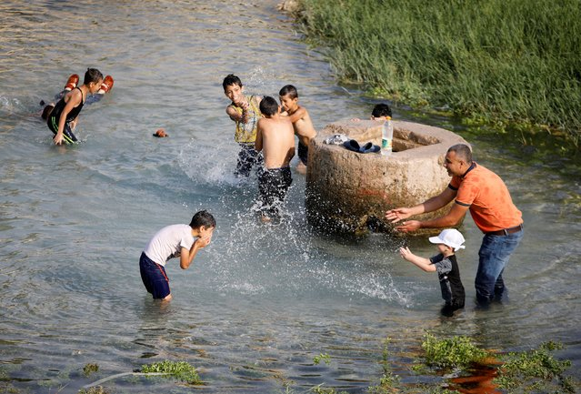 Palestinians cool off in the water of a natural spring during a heat wave, amid the coronavirus disease (COVID-19) crisis, near Tubas in the Israeli-occupied West Bank on August 30, 2020. (Photo by Raneen Sawafta/Reuters)