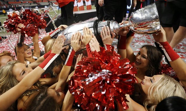 Calgary Stampeders cheerleaders celebrate with the Grey Cup after Calgary defeated the Hamilton Tiger Cats in the CFL's 102nd Grey Cup football championship in Vancouver, British Columbia, November 30, 2014. (Photo by Mark Blinch/Reuters)