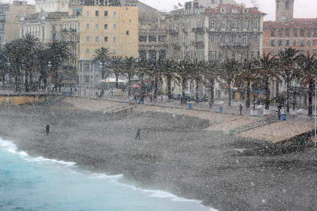 People walk through heavy snowfall along the Promenade des Anglais on February 26, 2018 in Nice. A wave of Siberian cold settled February 26 on the European continent, already contributing to at least nine deaths. (Photo by Valery Hache/AFP Photo)