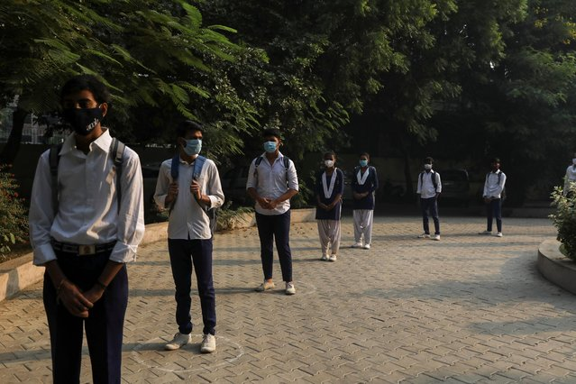 Students wearing protective face masks maintain social distance and stand in a line at a government-run school after authorities ordered schools to reopen voluntarily for classes 9 to 12, amidst the coronavirus disease (COVID-19) outbreak, in Gurugram India, October 15, 2020. (Photo by Anushree Fadnavis/Reuters)