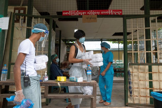 Volunteers wearing face shield and other protective equipments work at a quarantine center, amid the outbreak of the coronavirus disease (COVID-19), in Yangon, Myanmar, September 24, 2020. (Photo by Shwe Paw Mya Tin/Reuters)