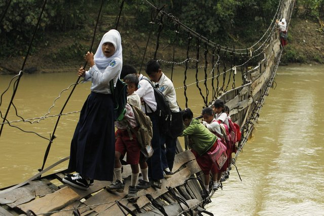 Students hold on to the side steel bars of a collapsed bridge as they cross a river to get to school at Sanghiang Tanjung village in Lebak regency, Indonesia's Banten village January 19, 2012. Flooding from the Ciberang river broke a pillar supporting the suspension bridge, which was built in 2001, on Monday according to Epi Sopian the head of Sanghiang Tanjung village. Sofiah, a student crossing the bridge, says she will need to walk for an extra 30 minutes if she were to take a detour through another bridge. (Photo by Beawiharta/Reuters)