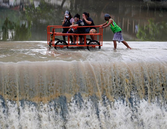 Villagers riding a rickshaw maneuver along an overflowing dam at the border between Cavite province and Las Pinas city, in Las Pinas, Philippines, 25 October 2020. According to Philippine Atmospheric Geophysical and Astronomical Services Administration (PAGASA), Typhoon Molave will make landfall in the evening of 25 October in southern Luzon island. An alert was issued to residents for possible floods and landslides. (Photo by Francis R Malasig/EPA/EFE)