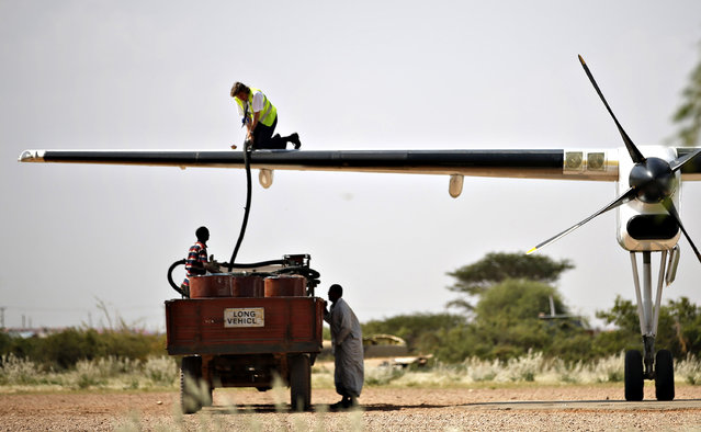 Men refuel an airplane in town of Mandera at the Kenya-Somalia border December 6, 2014. (Photo by Goran Tomasevic/Reuters)