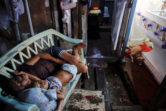 The wife and daughter of a man who was killed during a drug buy-bust operation sleep next to his coffin as relatives and friends gather to mourn outside his home in Manila, Philippines October 9, 2016. (Photo by Damir Sagolj/Reuters)