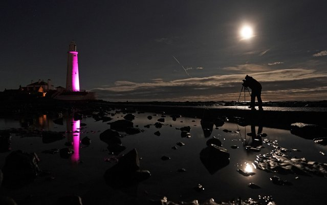 An almost full moon shines down over St Mary's lighthouse at Whitley Bay, Tyne and Wear on December 5, 2017, as a photographer lines-up a shot while waiting for the Northern Lights to appear in the sky. (Photo by Owen Humphreys/PA Images via Getty Images)