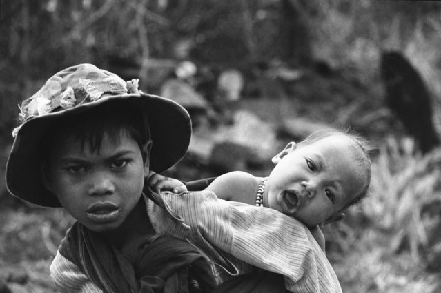 A young boy carries his brother on his back as his family flees fighting, March 15, 1975 at Pleiku in the central highlands of South Vietnam.  Fears of the North Vietnamese onslaught on the city caused South Vietnam to shift its regional command headquarters from Pleiku to the coast Saturday and the U.S. Embassy has evacuated almost all Americans from the area. (Photo by AP Photo)