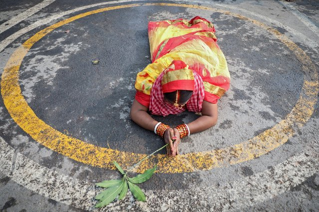 A Hindu devotee lies on the banks of river Ganges she worships the Sun god during the religious festival of Chhath Puja, amidst the spread of the coronavirus disease (COVID-19), in Kolkata, India November 20, 2020. (Photo by Rupak De Chowdhuri/Reuters)